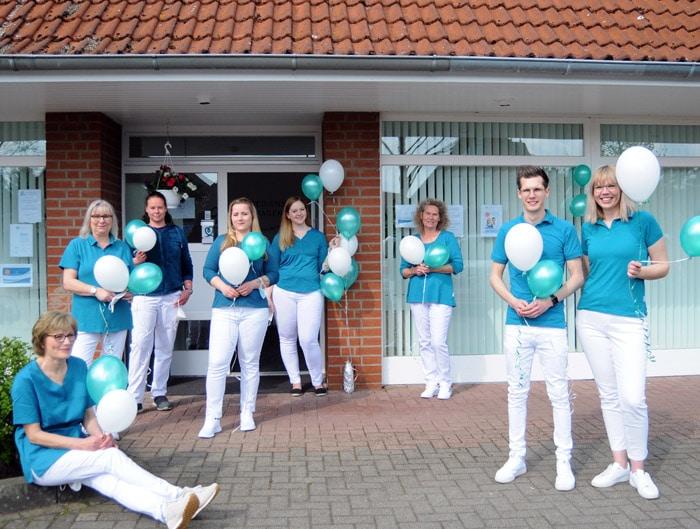 Das Team steht am Tag der Eröffnung mit Luftballons vor dem Büro